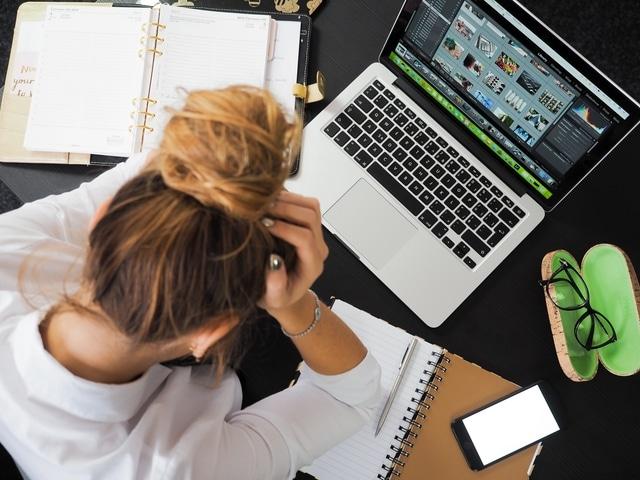 Femme stressée devant son travail et en manque de sommeil.